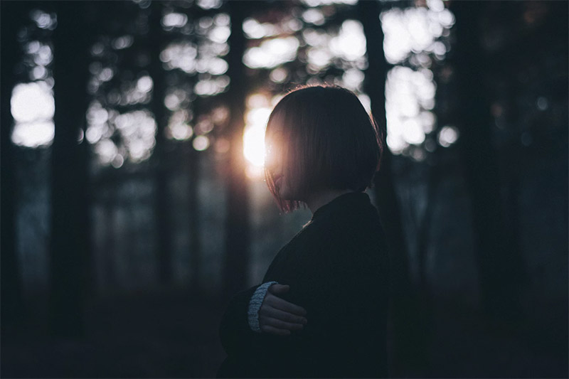 Sad woman in forest, sunlight behind here