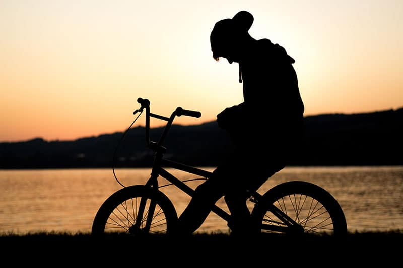 Silhouette of a person on a bicycle, grieving