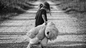 Sad girl, walking away with her teddy bear