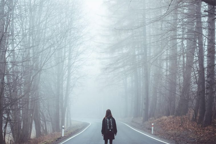 Girl alone in the forest, with a road before her